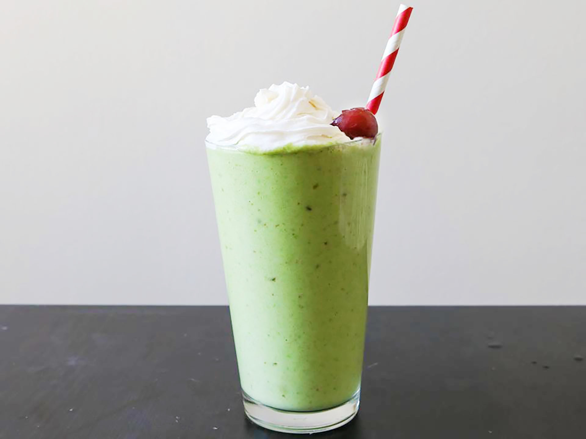 Tall glass of shamrock shake with whipped topping and a cherry