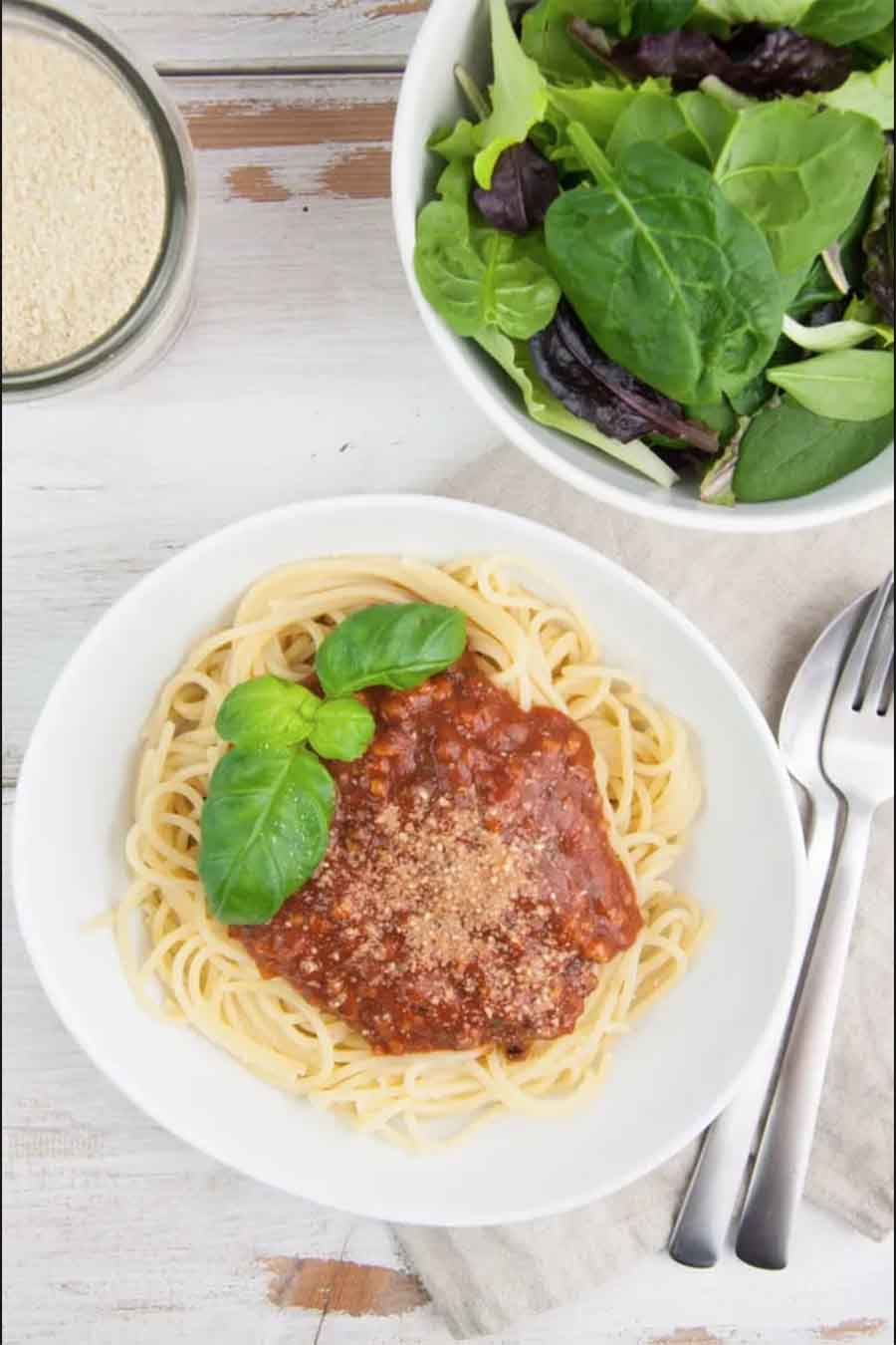 A white bowl of spaghetti bolognese with a side salad
