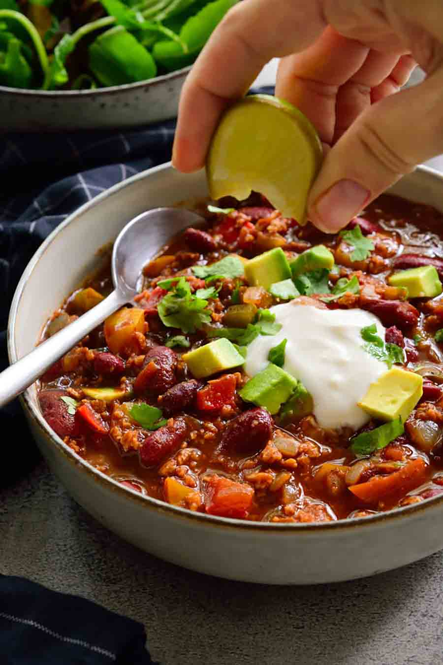 Bowl of chili with someone squeezing a lime on top