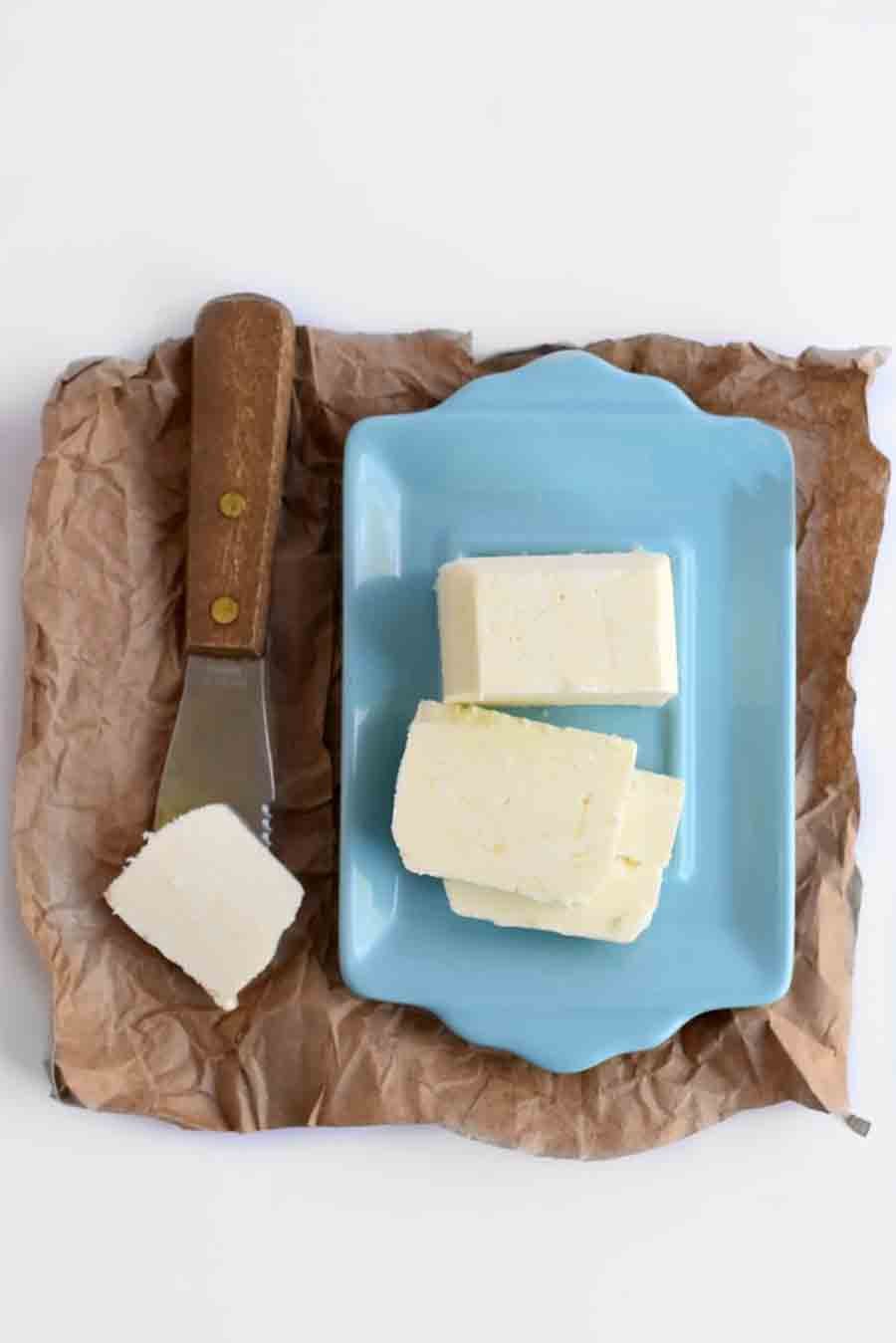 A blue dish of butter sitting on brown paper with a knife alongside