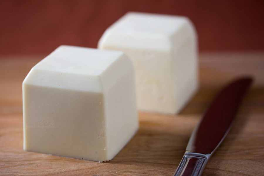 Two cubes of vegan butter sitting on a table near a knife