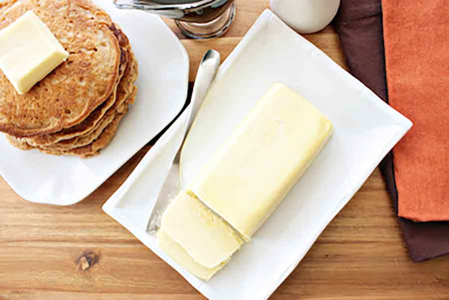 A dish of butter sitting on a wooden table near a stack of pancakes
