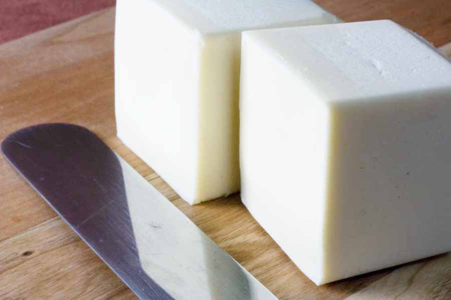 Two cubes of butter on a wooden board near a knife