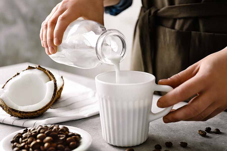 Person pouring creamer into a white coffee mug on a table with a bowl of coffee beans and a halved fresh coconut